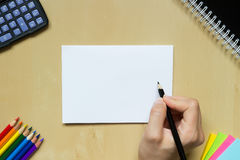 Hand med en penna på ett skrivbord Arkivfoto