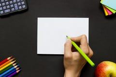 Hand med en penna på ett svart skrivbord Royaltyfria Bilder