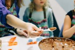 Hand med en sked, hemlagad stekflott för chokladsirap från en sked in i en bunke, en mästarklass, i att laga mat choklad royaltyfri fotografi