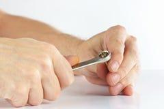 Hand med en skiftnyckel som drar åt muttern Royaltyfri Fotografi