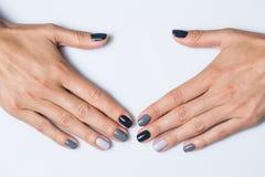 Hand med en stilfull grå manikyr som isoleras på arkivfoto
