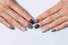 Hand med en stilfull grå manikyr som isoleras på royaltyfri foto