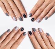 Hand med en stilfull grå manikyr som isoleras på fotografering för bildbyråer
