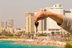 Hand med en tangent i bakgrunden av havet med byggnader och Fotografering för Bildbyråer