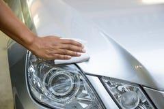 Hand med en wipe bilpoleringen Arkivbild
