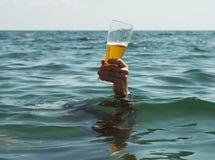 Hand med ett exponeringsglas av öl Arkivfoto