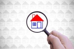 Hand med ett förstoringsglas som söker för ett hem för hyra Arkivbilder