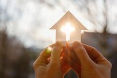 Hand med ett hus från papper och ett kors arkivbild
