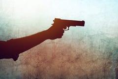 Hand med ett vapen på grungebakgrund Arkivfoto