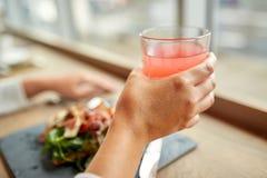 Hand med exponeringsglas av fruktsaft och sallad på restaurangen Royaltyfria Bilder