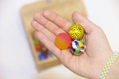 Hand med färgrika bollar och ask mycket av färgrika bollar Arkivbilder