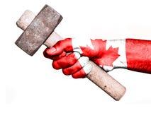 Hand med flaggan av Kanada som behandlar en tung hammare Royaltyfria Bilder