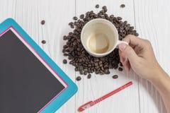 Hand med gröngölingen av kaffe och minnestavlan på den vita tabellen Royaltyfri Fotografi