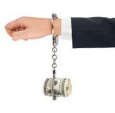 Hand med handbojor och pengar Royaltyfri Bild