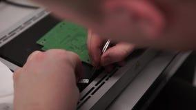 Hand med hjälpmedlet som reparerar mobiltelefonen och andra grejer Mikrochipsproduktionfabrik Teknologisk behandling monterar stock video