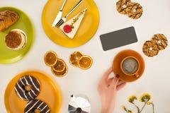 hand med kaffe och kakor royaltyfria foton