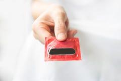 Hand med kondomen Royaltyfri Fotografi