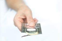 Hand med kondomen Royaltyfri Bild