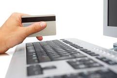 Hand med kreditkort- och datoronline-betalning arkivbild