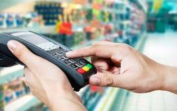 Hand med kreditkorthårda slaget till och med betalningterminalen Arkivbild