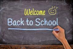 hand med krita tillbaka till skolan på svart tavla Royaltyfri Fotografi
