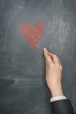 Hand med kritateckningen en hjärta Arkivfoto