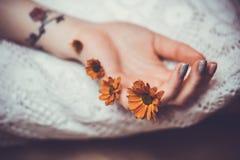 Hand med limmade blommor Arkivfoto