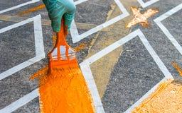 Hand med målarfärgborsten som målar vägen ingen gul linje område för parkering Royaltyfria Foton