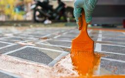 Hand med målarfärgborsten som målar vägen ingen gul linje område för parkering Royaltyfri Fotografi