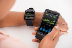 Hand med mobilen och hastighet för Smartwatch visninghjärtslag Arkivbild