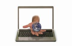 Hand med modellen av planeten som når ut ur bärbar datorskärm Royaltyfri Fotografi