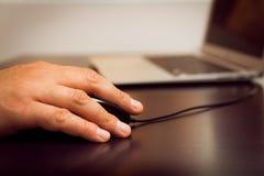Hand med musen, bärbar dator arkivbild