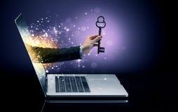 Hand med nyckel- komma ut ur en bärbar dator royaltyfri bild