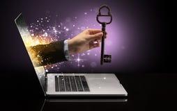 Hand med nyckel- komma ut ur en b?rbar dator fotografering för bildbyråer