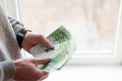 Hand med pengar n?gra hundra euro i sedlar arkivbilder