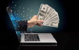 Hand med pengar som kommer ut ur en bärbar dator arkivfoton