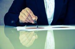 Hand med pennan och graf på papper Fotografering för Bildbyråer