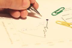 Hand med pennan och växande diagram i papperet Royaltyfri Foto
