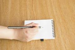 Hand med pennan som ner skriver anmärkningar Royaltyfri Foto