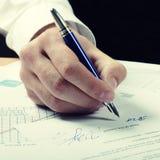 Hand med pennan som undertecknar ett dokument Royaltyfria Bilder