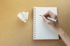 Hand med pennhandstil på den tomma spiralanteckningsboken royaltyfri bild