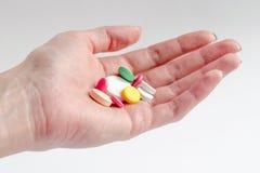 Hand med pills royaltyfria bilder