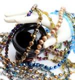 Hand med pärlor, pärlor och kristallkula Arkivfoto