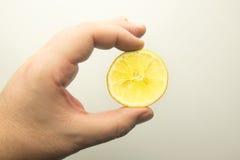 Hand med skivan av den gula citronen Royaltyfri Fotografi