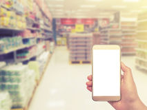 Hand med smartphonen på suddigt i varuhus Arkivfoton
