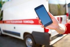 Hand med smartphonen som kallar på nöd- bilbakgrund Arkivfoton