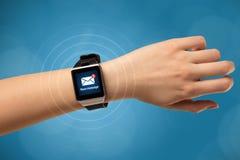 Hand med smartwatch- och blåttbakgrund Arkivfoton