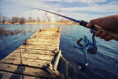 Hand med snurr och rulle på aftonsommarsjön Arkivfoton