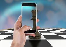 Hand med telefonen mot schackstycke och blåttbokeh Arkivfoton