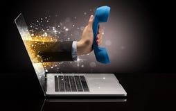 Hand med telefonen som kommer ut ur en bärbar dator royaltyfria foton